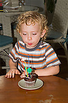 Blonde 3+ boy blows out candle on a chocolate cupcake on his birthday indoors