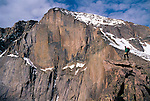 Man pauses on a rock ledge while looking at East Face of Longs Peak, Rocky Mtn Nat'l Park, CO, USA