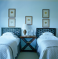 In the guest bedroom an antique folding table has been placed between the beds which have wooden headboards in an intricate latticework pattern