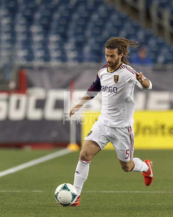 Real Salt Lake midfielder Kyle Beckerman (5) brings the ball forward.  In a Major League Soccer (MLS) match, Real Salt Lake (white)defeated the New England Revolution (blue), 2-1, at Gillette Stadium on May 8, 2013.
