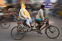 Motion Blur of man riding on a local rickshaw at India's Pushkar Camel Fair, Pushkar, Rajasthan, India