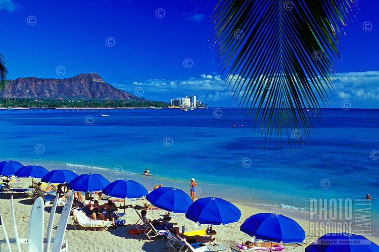 Vacationers enjoy a view of Diamond Head Crater as they relax on the inviting sands of Waikiki Beach.This photo taken from the Outrigger Reef on the Beach Hotel.
