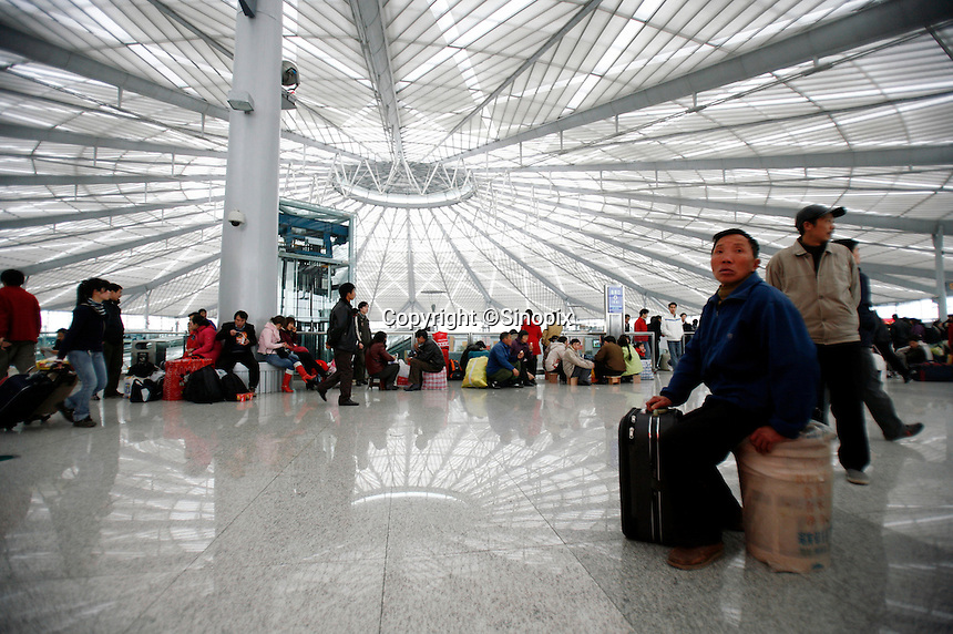 A migrant worker sits on his belonging while waiting for his train at the futuristic South Railway Station in Shanghai, China. With the Chinese New Year only one week away, millions of Chinese are traveling in hopes of spending this most important of traditional Chinese holidays with their family..9 Feb 2007