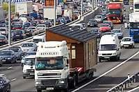 Prefabricated house being transported by road on truck in congested traffic on M25 motorway, London, United Kingdom