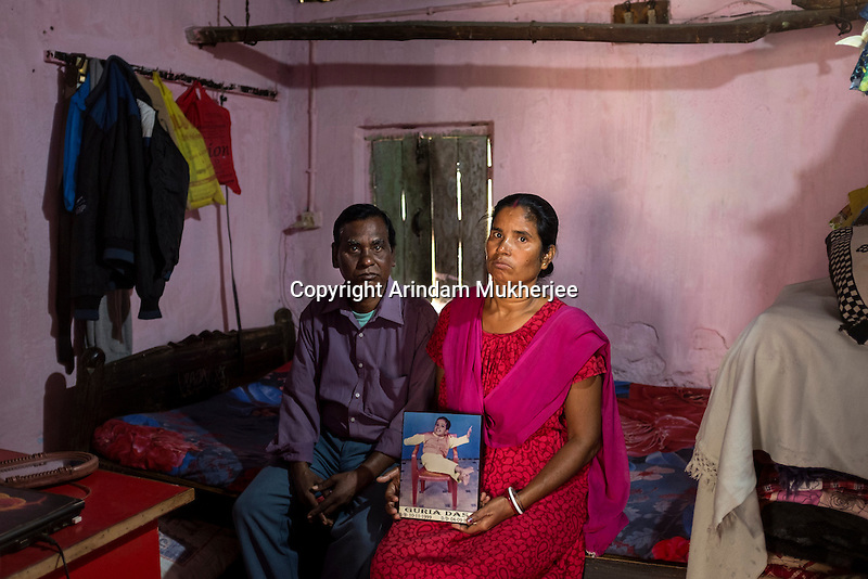 Chhatua Das, 46, and his wife Lakshmi Das, 35, with a photograph of their daughter Guria, who died in 2012. She was 13 when she died but she looked no more than five or six. Guria could not speak, walk or eat solid food. Lakshmi also had a miscarriage, and another child was stillborn.