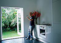 Owner Martin Barrell looking out of the double doors to the garden from his kitchen