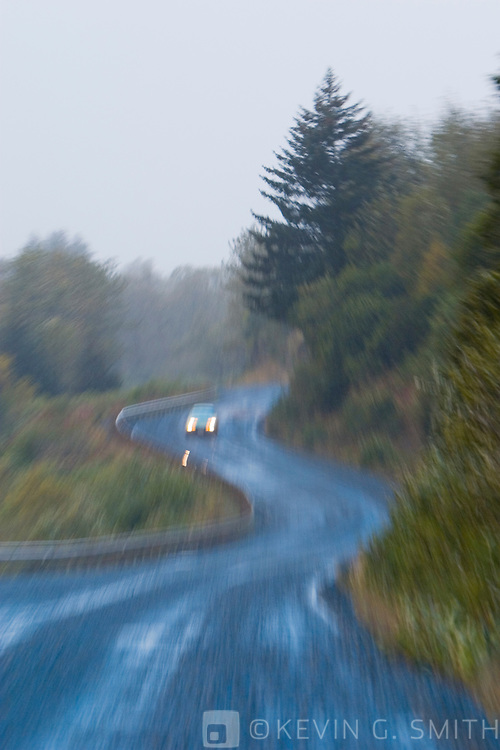 Car on curvey gravel road in the rain, motion blur, fog, fall, Cape Chiniak Road, Kodiak Island, Alaska, USA.