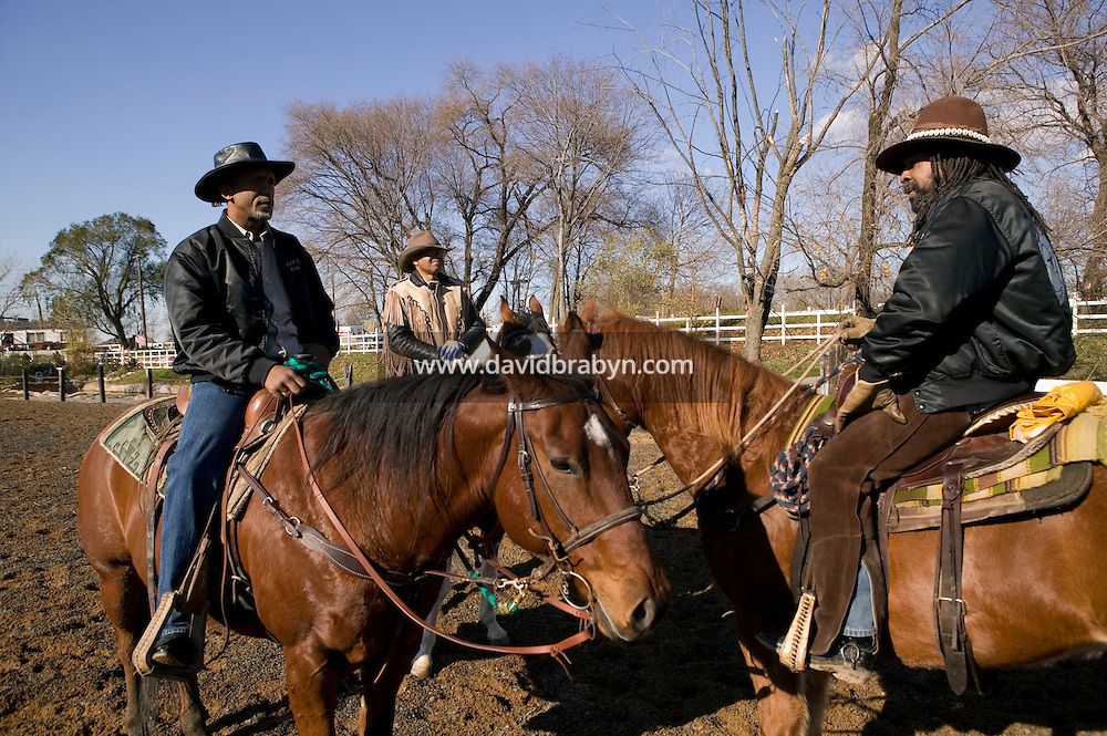 2 December 2006 - New York City, NY - Eric Jackson (L), aka Cowboy Little Red, R. W. Hall (C), aka Curly, and Lenard Hebert, members of the Federation of Black Cowboys, chat on horseback at the Cedar Lanes stables in the borough of Queens in New York City, USA, 2 December 2006. The Federation gathers black men and women who recreate the heritage of black cowboys, teach kids to ride and put on 'rodeo showdeos'.