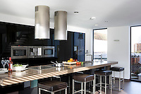 In the kitchen/living area a set of matching kitchen stools in brown leather and stainless steel are ranged along one side of the long floating island constructed from mellow Quartz stone