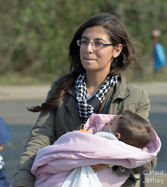 A refugee woman holds her child at the border crossing into Austria near the Hungarian town of Hegyeshalom. Hundreds of thousands of refugees and migrants--including many children--flowed through this region in 2015 on their way to western Europe from Syria, Iraq and other countries. The ACT Alliance has provided food and other critical support for refugee and migrant families here and in other places along their journey.