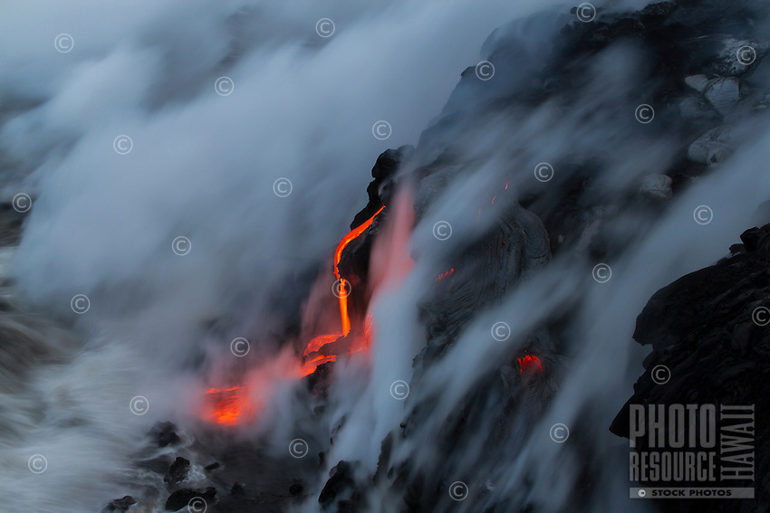 A lava tube flows into the sea, cooling in the midst of intense smoke, Hawai'i Volcanoes National Park, Big Island.