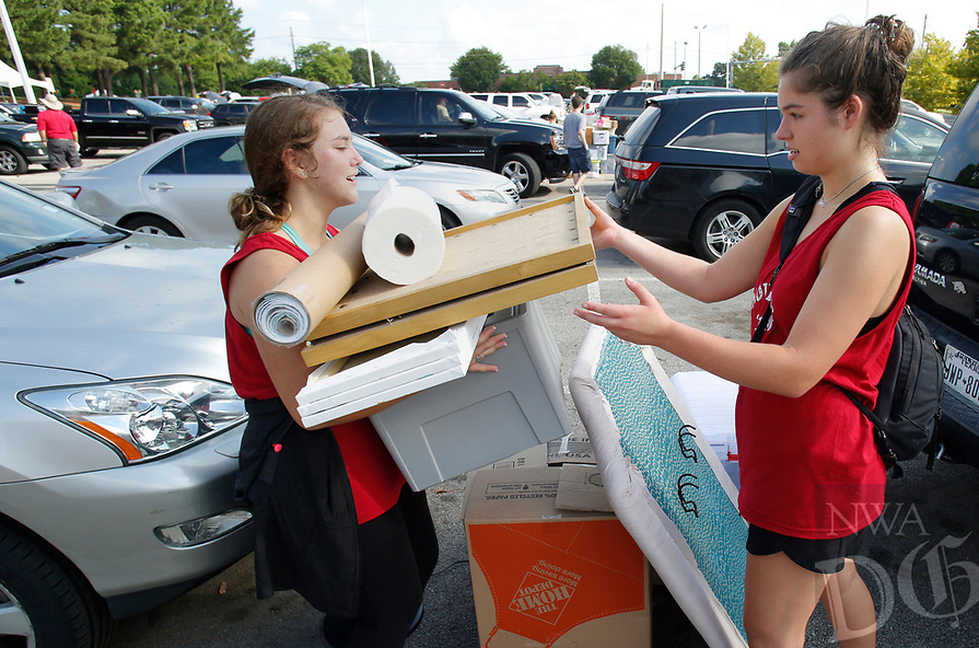 NWA Democrat-Gazette/DAVID GOTTSCHALK Mollie Henry (left), a sophomore and Claire Cain, a junior, both volunteers help carry items to a dorm room on the first day of Move-in for the 2018-2019 school year on the campus of the University of Arkansas in Fayetteville. University Housing coordinates the effort and staff expect more than 5,200 students to be moving into residence halls during this period.