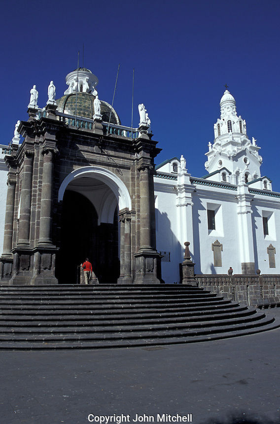 Woman entering the neoclasical style cathedral in old Quito, Ecuador. Old Quito was made a UNESCO World Heritage Site in 1978.