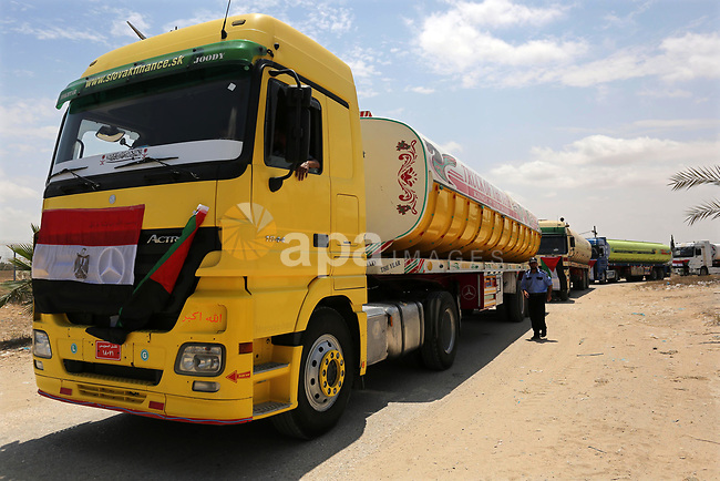 A member of Palestinian security forces stands guard as Egyptian trucks carrying fuel enter the southern Gaza Strip from Egypt through the Rafah border crossing on June 21, 2017. Egypt began to deliver a million litres of fuel to Gaza, a Palestinian official said, in an attempt to ease the Palestinian enclave's desperate electricity crisis. The fuel, trucked in through the Rafah border between Egypt and Gaza, will be routed to the territory's only power station -- closed since April due to fuel shortages. Photo by Ashraf Amra