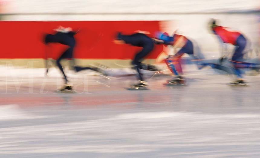 Blurred motion image of speed skaters in competition.