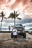 USA, Oahu, Hawaii, Daytyn Ragragola stands in front of his enormous pickup truck on the North Shore at Haliewa Beach Park