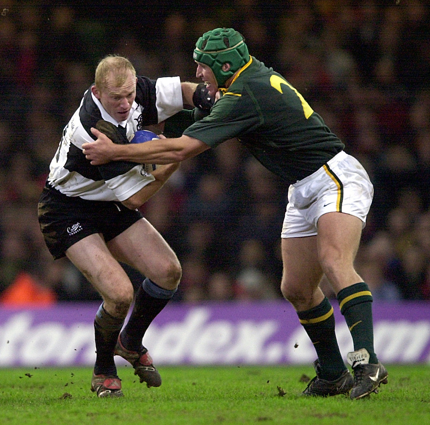 Photo. Richard Lane. .Barbarians v South Africa at the Millennium Stadium, Cardiff. 10-12-2000. The Scottish Amicable Challenge..Neil Jenkins gets caught by Dan van Zyl.