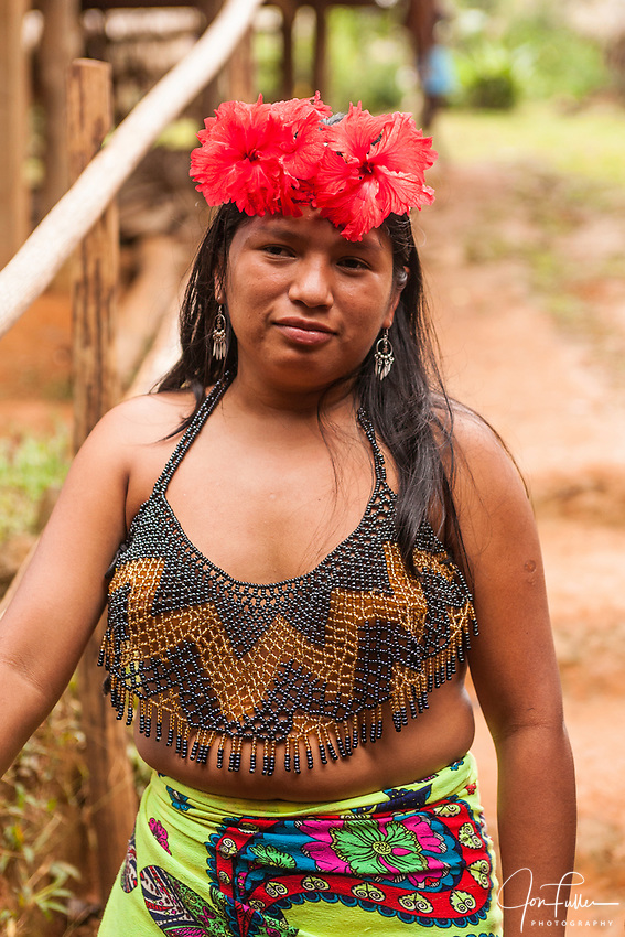 An indigenous Embera woman dressed up for visitors in her village on Lake Alejuela in Panama.  The women's tops are beaded and often decorated with silver coins. Chagres National Park
