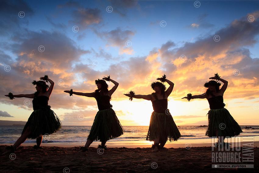 Silhouette of hula dancers at suset at Palauea Beach, Maui, Hawaii.