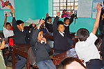 Boys and girls in uniforms in elementary class raise their hands in classroom in Peruvian school.