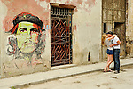 HAVANA - JANUARY 3: A couple embrace and kiss in front of a building with Che Guevara graffiti drawn on it in Havana, Cuba.