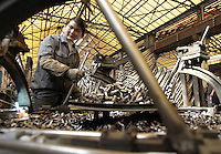 Surrounded by piles of metal, a female worker makes bicycle forks at the Shanghai Forever Bicycle Factory (SFBF) in Shanghai, China. Despite the government's efforts to encourage automobile ownership in recent years, the bicycle remains the most popular mode of transportation for China's masses. The SFBF, it's products once a must have and a symbol of status for every Chinese family, are now supplying bicycles to countries around the world. It has seen it's sales increase 59% percent in the past year to 876 million yuan (euro 89.36 million)..21-APR-04
