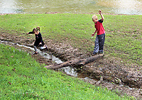 MEGAN DAVIS/MCDONALD COUNTY PRESS 4-year-old Briella Kellogg and 8-year-old Ayden Kellogg took advantage of the flooded Honey Creek and turned the terrain into an obstacle course on Saturday afternoon.