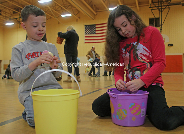 Winsted, CT-032313MK12  (from left) Robert Leonard (5) and his sister Avery Leonard (8) look over the surprises they found in the eggs they collected during the annual easter egg hunt at Person Middle School in Winsted on Saturday morning.  Tricia Twomuy, parks and recreation director, said that volunteers placed 1500 eggs for the activity.  Approximately 150 children participated in two different aged group hunts.  One was for toddlers to four years and one for five to eight year olds. Michael Kabelka Republican American