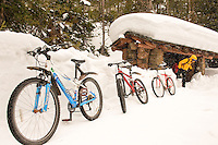 High snow banks and passing squalls are part of what makes spring biking in Yellowstone National Park so much fun. Tara Kramer emerges from the shelter of an interpretive display near Obsidian Cliff.