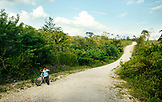 BELIZE, Punta Gorda, Toledo, a boy walks his bike down the road near the ruins of Lubantuun