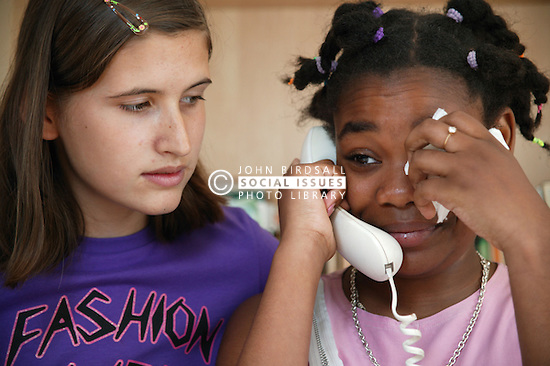 Teenage girl comforting her friend who is crying on the telephone,