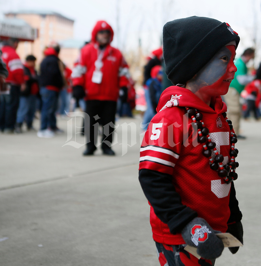 OhioState Buckeye fan Preston Garinger 3 from Hillard holds onto his ticket while entering with dad Dave Garinger at Ohio State Stadium in Columbus  Nov. 23, 2013.