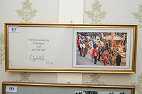 BNPS.co.uk (01202 558833)<br /> Pic: PhilYeomans/BNPS<br /> <br /> Royal Christmas cards sent from the Queen.<br /> <br /> A remarkable 'timewarp' archive amassed by a dressmaker to the Queen has sold for over £100,000.<br /> <br /> The late Ian Thomas meticulously kept his fashion designs, letters, cards and photographs relating to the Queen at his home that was more like a museum. <br /> <br /> He helped design the Queen's coronation gown in 1953 as well as the powder blue outfit she wore for Charles and Diana's wedding in 1981.<br /> <br /> The lifelong bachelor passed away in 1993 and left his home and its contents to a florist he had been good friends with for 25 years.<br /> <br /> After she died in 2015 the property was inherited by a relative who also knew Mr Thomas well.<br /> <br /> She has now sold the contents at auction.