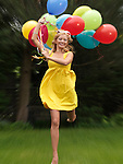 Young happy woman running with a bunch of colorful air balloons