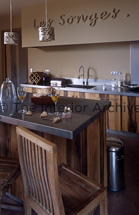 A contemporary kitchen with a rustic edge - stainless steel work surfaces combine with rustic wooden units