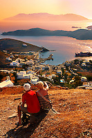 Older couple sitting on the top of Chora Mountain looking across the harbour of Ormos, Ios,  Cylades Islands, Greece