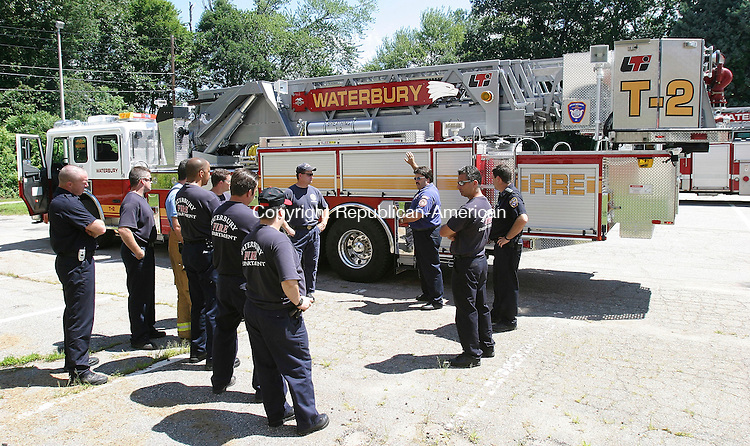 WATERBURY, CT 23 July 2005 -072305BZ02- <br /> Waterbury firefighters listen to Michael Couture, of the CT Fire Academy,  center of group with arms raised, as he talks about the department's newest piece of apparatus during training at Naugatuck Vallley Community College.<br /> Couture is also a Captain in the Waterbury Fire Department training division. <br /> Jamison C. Bazinet Photo
