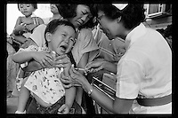 A young boy receives an inoculation during a cholera outbreak in Hong Kong, 1986.