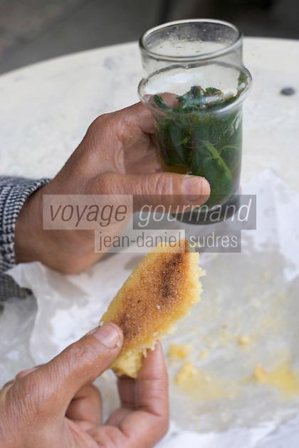 Afrique/Afrique du Nord/Maroc/Fèz: Médina de Fèz-El-Bali prés de la porte Bleue un homme prend son petit déjeuner avec du thé à la menthe et de la Harcha pain plat à la semoule e blé