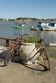 Ilheus, Bahia State, Brazil. Old bicycles with a planter, fishing boats on the Bahia de Pontal.
