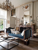 A traditional sitting room with neutral painted walls with gilded mouldings. A simple, modern coffee table is placed in front of a day bed with a blue cushion. A built-in mirror hangs above the marble fireplace.