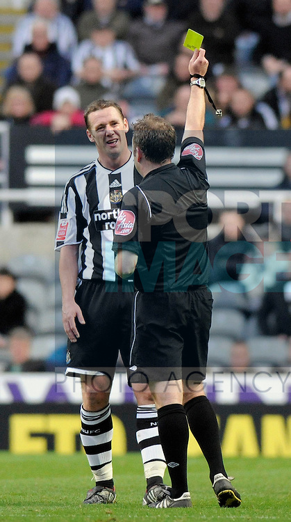 Newcastle's Kevin Nolan is shown his first yellow card by referee Jonathan Moss.