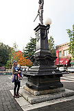 USA, Oregon, Ashland, a local woman Dana stands with her baby Olivia in front of a sculpture in the town square in downtown Ashland