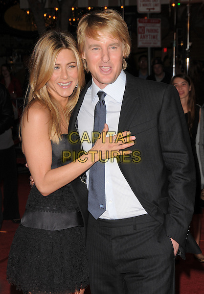 "JENNIFER ANISTON & OWEN WILSON.The Twentieth Century Fox World Premiere of ""Marley & Me"" held at The Mann Village Theatre in Westwood, California, USA. .December 11th, 2008 .half length black grey gray strapless silk satin top skirt dress frills ruffled ruffles blue tie white shirt suit jacket ring hand on chest stomach.CAP/DVS.©Debbie VanStory/Capital Pictures."