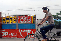 A cyclist passes a factory that recycles rubbish and uses rubbish to cover it's gate from the United Kingdom's Tesco is recycled in Mai village, Shunde, China.  There is so much re-cycling in the area that the waste plastic spills out into streams and farmland polluting the environment.<br /> <br /> Photo by Richard Jones/ Sinopix