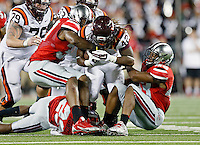 Ohio State Buckeyes linebacker Joshua Perry (37), left, and Ohio State Buckeyes linebacker Darron Lee (43) try to get the ball away from Virginia Tech Hokies running back Marshawn Williams (42) during the 1st quarter of their game in Ohio Stadium on September 6, 2014.  (Dispatch photo by Kyle Robertson)