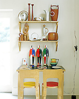 A collection of kitchen equipment and containers is displayed on two open shelves above a plywood side table and matching chairs