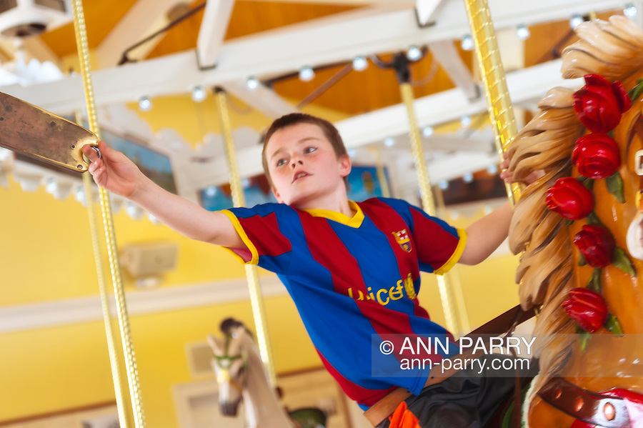 Jack Neary hopes to grab a brass ring while riding historic Nunley's Carousel during its Centennial Celebration on Saturday, June 9, 2012, at Museum Row, Garden City, Long Island, New York, USA. Though most rings are steel, a carousel rider who grabs a brass ring wins a free ride.