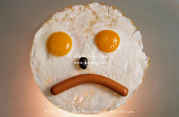 Fried breakfast of eggs and sausage made into a frowning face.