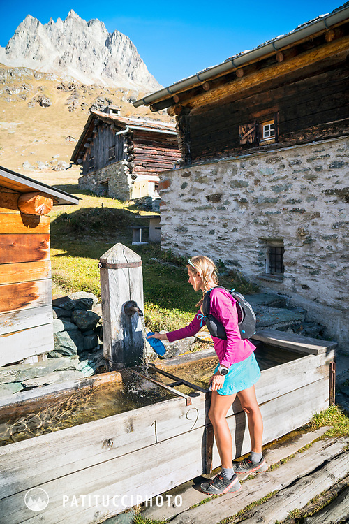 A trail runners fills her water bottle at a fountain in Grevasalvas, near Maloja, in the Engadin, while on a running tour to Piz Lunghin. Switzerland.